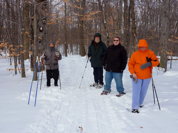 Group snow shoeing on a trail. Group: Robert Rogers on the far left, then on the right is Ken Bordwell, Victoria Bordwell, and Joyce Rogers.