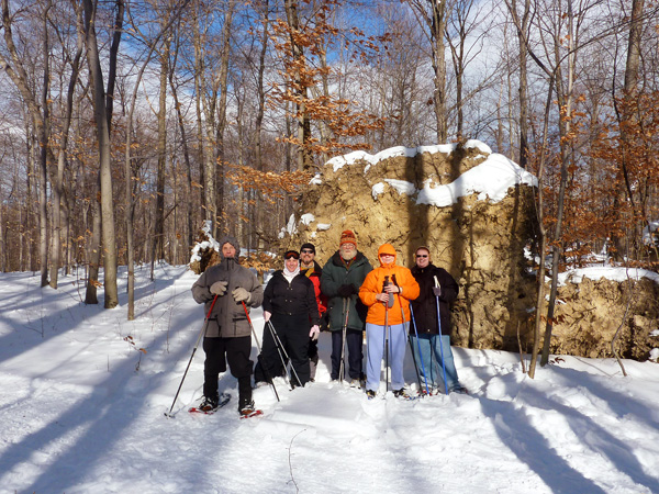 Snow shoeing group. There is a big boulder in the backround with some trees on the left and right. Shown from Left to right are: Robert Rogers, Catherine Bister, Roger Meridith, Ken Boardwell, Joyce Rogers, and Victoria Bordwell.